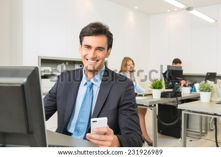 Young executive sitting at his desk, holding a Smartphone - stock photo