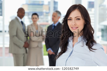 Young executive smiling and standing in a bright room with her team behind her - stock photo