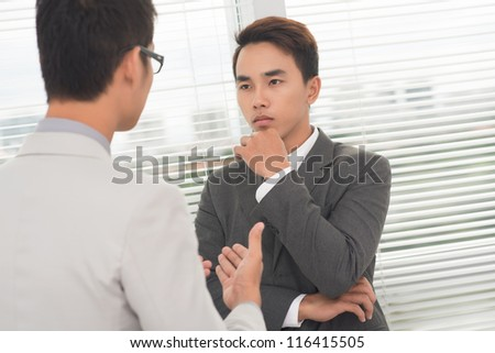 Young executive thinking over what his partner is saying - stock photo