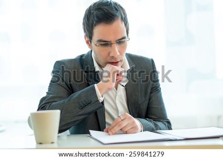 Young executive thoughtfully and attentively reading a job application while sitting at his desk and enjoying a cup of coffee. - stock photo