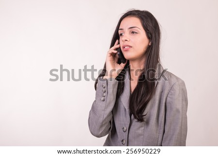 Young executive woman dressed in grey and with a cellular looking at the side - stock photo