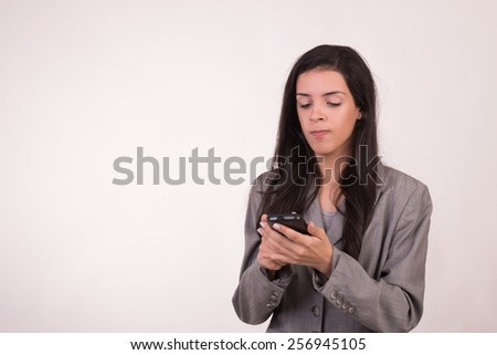 Young executive woman dressed in grey and with a cellular texting with anger - stock photo