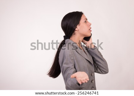 Young executive woman dressed in grey and with a cellular with shocked face - stock photo