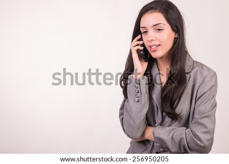 Young executive woman dressed in grey listening on cellphone smiling and her hands folded - stock photo