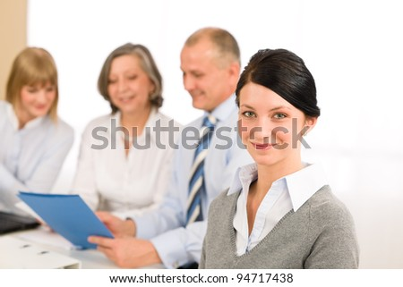 Young executive woman looking camera during meeting with team colleagues