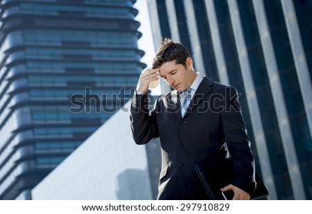 young exhausted and worried businessman standing outdoors on street in front of business buildings at financial district looking sad in work stress and headache holding take away coffee - stock photo