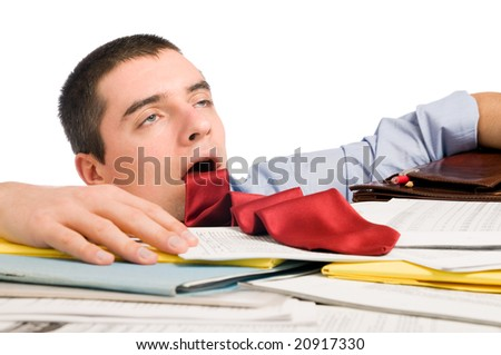 Young exhausted businessman with his necktie like a stuck out tongue lying down heap of documents. - stock photo