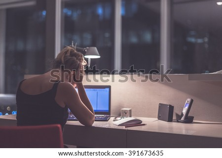 Young exhausted,depressed,concentrated woman sitting in her room or office with french windows in the dark.Studies late at night.Staying up late. Overworking.Feeling under pressure and headache - stock photo