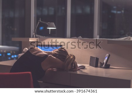 Young exhausted  woman sleeping at the desk in her room or office with french windows  in the dark at the lamp.Studies late at night.Staying up late. Overworking.Meeting deadline. - stock photo