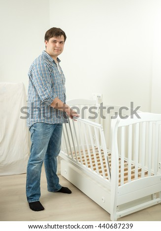 Young expectant father assembling bed for his future baby