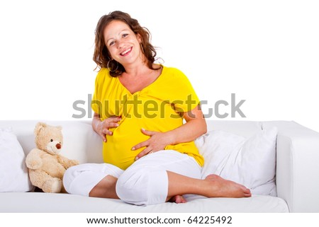 Young expecting mother is sitting on a couch at home. Highkey image over pure white background. - stock photo