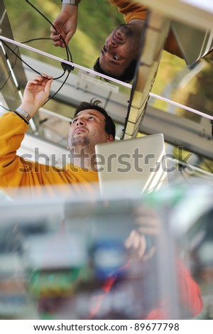 Young expert engineer working, using laptop and connecting wires - stock photo