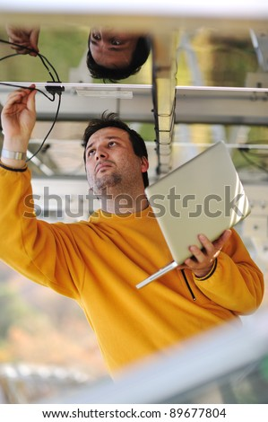 Young expert engineer working using laptop and connecting wires - stock photo