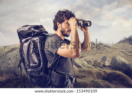 young explorer in high mountain looks horizon with binoculars - stock photo