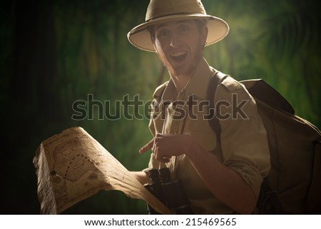 Young explorer in the jungle finding the right direction and holding an old map. - stock photo