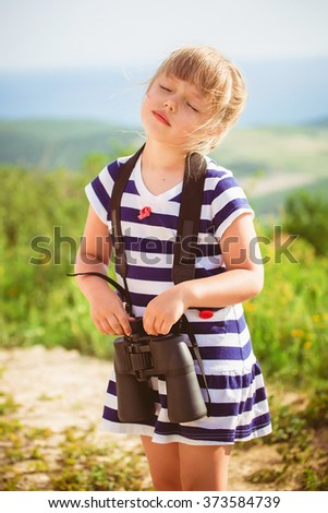 young explorer looks at the scenic view through binoculars - stock photo