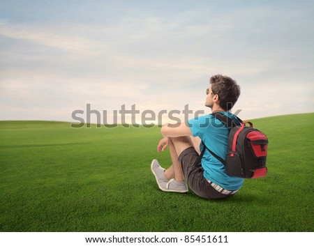 Young explorer sitting on a green meadow - stock photo