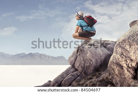 Young explorer sitting on a peak - stock photo