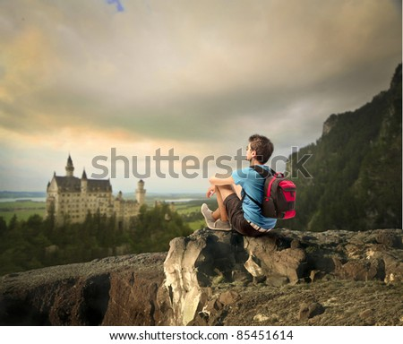 Young explorer sitting on a rock in front of a fairy tale castle - stock photo