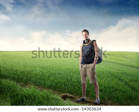 Young explorer standing on a green meadow - stock photo