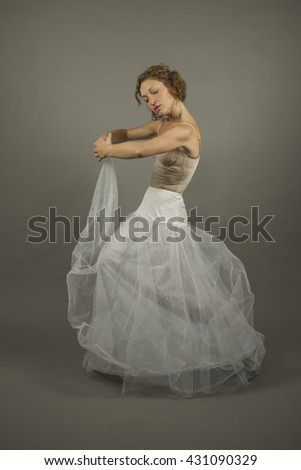Young expressive ballerina with a white long tutu practicing ballet by herself, isolated in a grey background - stock photo