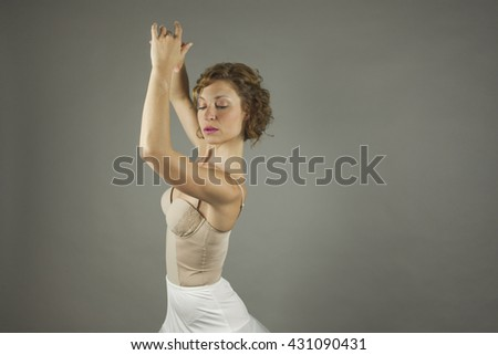 Young expressive ballerina with practicing ballet by herself, isolated in a grey background - stock photo