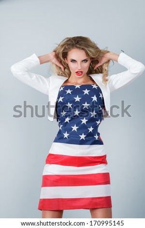 Young expressive blonde woman wrapped in american flag against studio background - stock photo