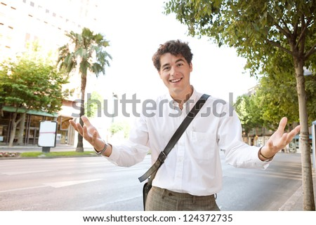 Young expressive businessman standing in a wide city avenue, having a conversation and gesturing with his arms and hands to the camera, outdoors.