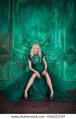 Young extravagant beautiful woman in the studio with hair and professional make-up in green vintage dress, bright red lips, blonde, thin waist, beautiful figure, fashion, magazine shooting