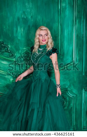 Young extravagant beautiful woman in the studio with hair and professional make-up in green vintage dress, bright red lips, blonde, thin waist, beautiful figure, fashion, magazine shooting - stock photo