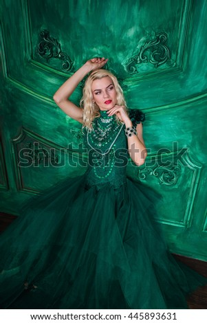 Young extravagant beautiful woman in the studio with hair and professional make-up in green vintage dress, bright red lips, blonde, thin waist, figure, fashion, magazine shooting - stock photo