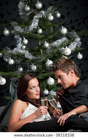 Young extravagant man and woman with champagne sitting in front of silver decorated Christmas tree - stock photo