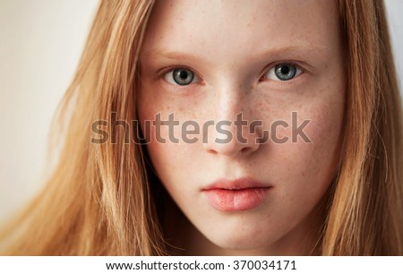 Young eyes girl beautiful redhead freckles woman face closeup portrait with healthy skin - stock photo