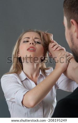 Young fair-haired woman holding man at his hand looking suppliantly at him while he grasps her hair. Isolated on grey background - stock photo
