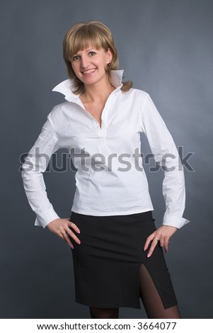 young fair-haired woman standing in white shirt and black skirt in modern office style - stock photo