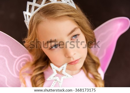 Young fairy in a pink shirt with a white crown on her head and pink wings holding a magic wand at face, close-up - stock photo