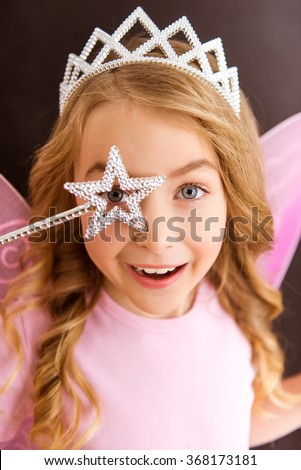 Young fairy in a pink shirt with a white crown on her head and pink wings looking through her magic wand, wind is close-up - stock photo