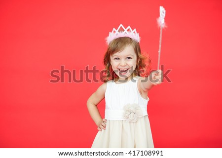 Young fairy in a white dress and crown holding a magic wand in her hand isolated over red background - stock photo