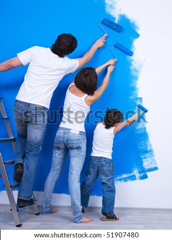 Young family brushing the wall together into the blue color - stock photo