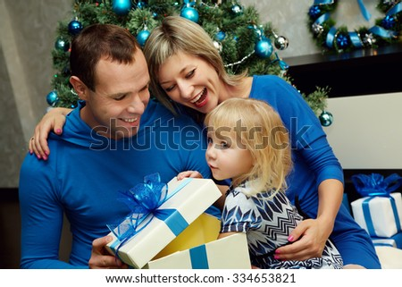 young family celebrating Christmas at home. father and mother give a child present. New Year and xmas people - stock photo