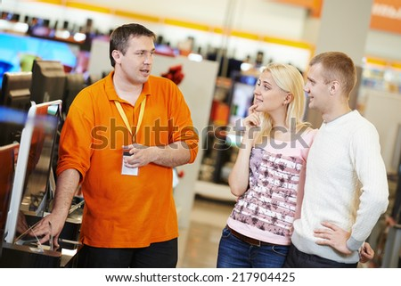 Young family choosing tv set with shop assistant in home appliance shopping mall supermarket - stock photo