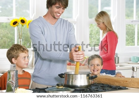 Young family cooking spaghetti with Dad placing the pasta in a pot closely watched by his two young children