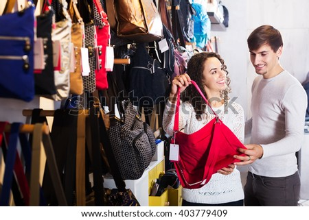 Young family couple buying leather bags in haberdashery shop - stock photo