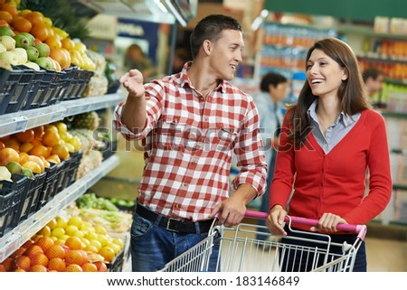 Young Family couple choosing bio food fruit in vegetable supermarket during weekly shopping - stock photo