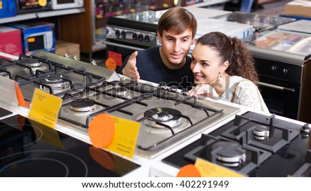 Young family couple choosing new gas-stove in appliances store - stock photo