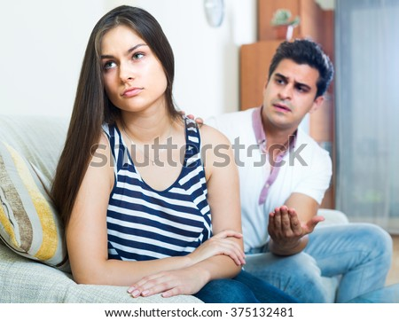 Young family couple having home quarrel in the living room - stock photo