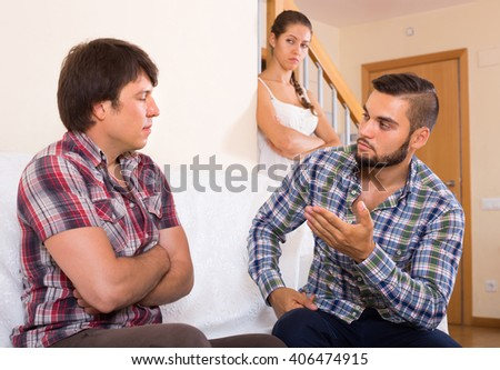 Young family couple having quarrel with neighbour indoor