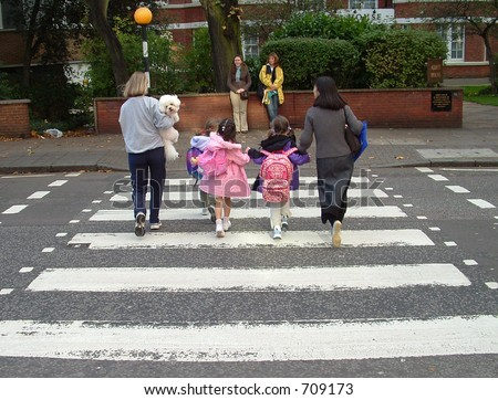 Young family crossing the famous abbey road crossing in londons west end.  Beatles done it years ago . but same crossing. - stock photo