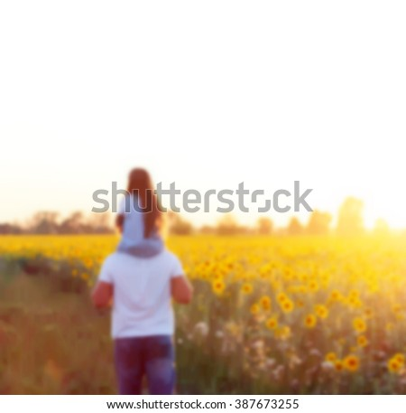 Young family (dad and daughter) in a field where people grow sunflowers on a bright Sunny day (blurred background) - stock photo
