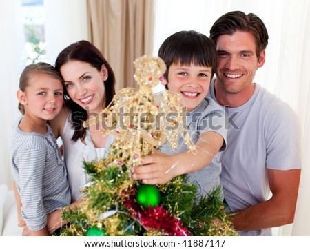 Young family decorating a Christmas tree in the living-room